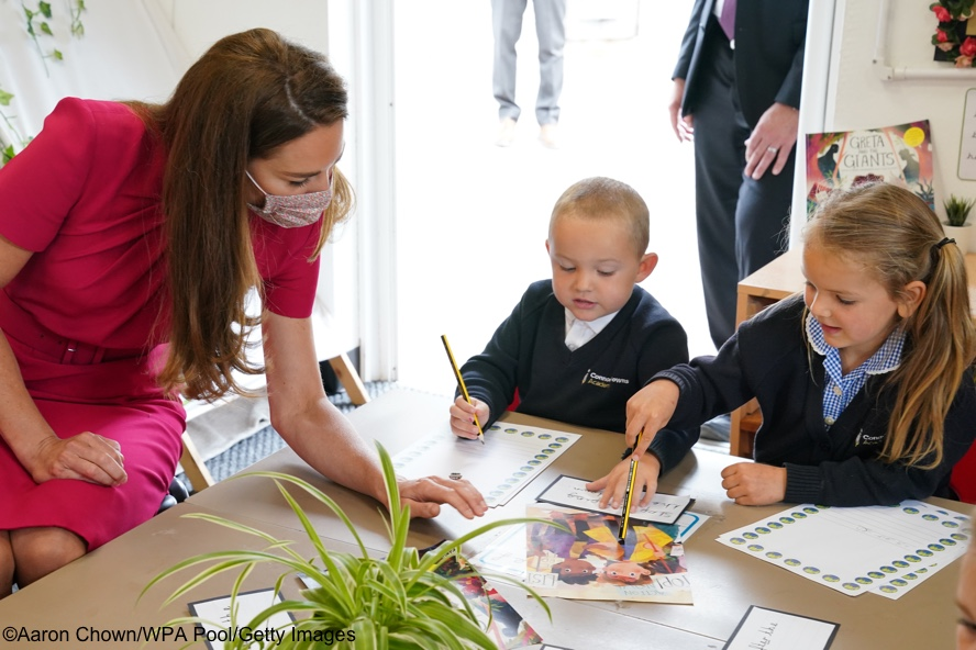 Kate-Leaning-over-Talking-to-Kids-School